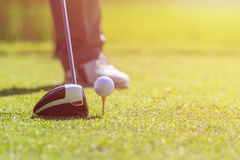A man playing golf in green course. Focus on golf ball stock image