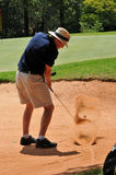 Man playing golf shot out of sand bunker on green Royalty Free Stock Photos