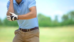 Man playing golf, suddenly feeling sharp elbow pain, massaging to relieve spasm