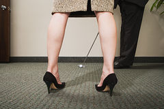 Man playing golf through woman's legs Stock Photos