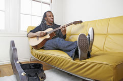 Man playing guitar. African American man reclined and playing acoustic guitar Royalty Free Stock Image