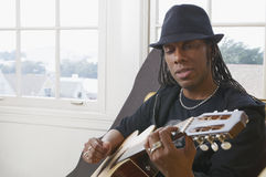 Man playing guitar. African American man wearing a hat and playing acoustic guitar Stock Photo
