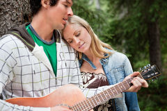 Man playing the guitar. Romantic couple with man playing the guitar stock photography