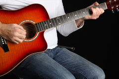 Man Playing a Guitar. Close up of a man playing an acoustic guitar with a black background Royalty Free Stock Image