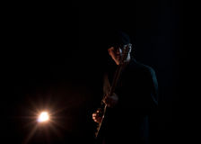 Man playing guitar. Man wearing a black hat , playing guitar on a black background Stock Photography
