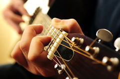 Man playing a guitar. Hands of a person playing an acoustic guitar close up Stock Image