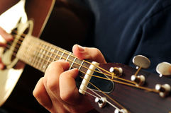 Man playing a guitar. Hands of a person playing an acoustic guitar close up Royalty Free Stock Images