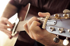 Man playing a guitar. Hands of a person playing an acoustic guitar close up Royalty Free Stock Photography