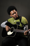 Man playing guitar. Portrait of young african american man playing acoustic guitar Royalty Free Stock Photography