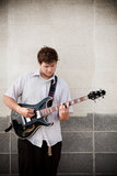 Man playing guitar against wall. Young man playing his hollow-body guitar - outdoors against wall royalty free stock photo