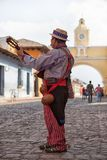 Man playing guitar in Antigua Guatemala. February 8, 2015 Antigua, Guatemala: man in traditional clothing playing guitar on the cobblestone street Royalty Free Stock Image