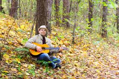 Man is playing a guitar in autumn forest Royalty Free Stock Image