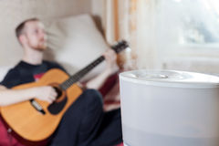 Man playing guitar on the background of humidifier Stock Photo