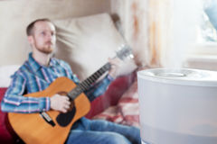 Man playing guitar on the background of humidifier Stock Images