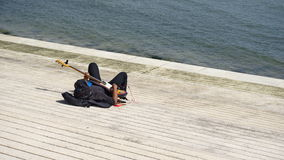 A man playing guitar on the beach in Lisbon. Musitian have a repetition right on a beach in Lisbon royalty free stock photo