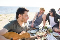 Man playing guitar on beach party Royalty Free Stock Photo