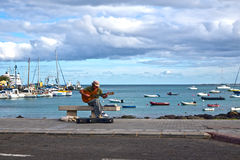 Man playing guitar on a bench by the harbor harbour. In Corralejo Canary-islands Spain No RF Royalty Free Stock Photography