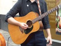 Man playing guitar. Brown instrument black shirt Stock Photos