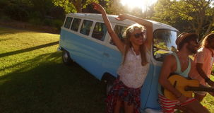 Man playing guitar in campervan and friends dancing beside him stock video footage