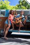 Man playing guitar in campervan and woman standing beside him Stock Images