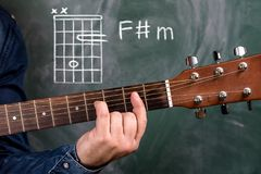Man playing guitar chords displayed on a blackboard, Chord F sharp m Stock Image