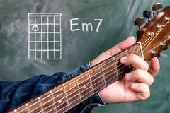 Man playing guitar chords displayed on a blackboard, Chord A minor 7. Man in a blue denim shirt playing guitar chords displayed on a blackboard, Chord A minor 7 Royalty Free Stock Photo