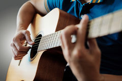 Man playing guitar. Closeup right hand of someone playing guitar on gray background Royalty Free Stock Photo