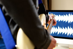 Man playing guitar with computer in background Royalty Free Stock Photography