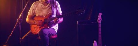 Man playing guitar at concert. Young man playing guitar at concert while sitting on stool in nightclub Stock Photo