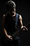 Man playing on the guitar in the dark Stock Photography