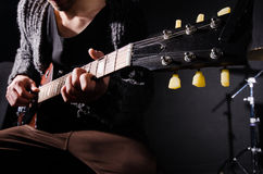 Man playing guitar in dark room. The man playing guitar in dark room Royalty Free Stock Photo
