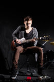 Man playing guitar in dark room Stock Photo