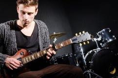 Man playing guitar in dark room Royalty Free Stock Image