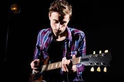 Man playing guitar in dark room Stock Images