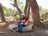 Man playing guitar in a desert camp. Senior man with cowboy hat on singing and playing a guitar while sitting on a rock near a red rock cliff in the desert Stock Images