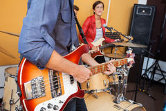 Man Playing Guitar With Female Singer In Recording. Midsection of men playing guitar with female singer in recording studio Royalty Free Stock Photo