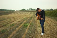 Man playing guitar. Man with guitar in field royalty free stock photo