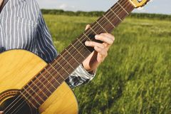 Man playing guitar on field Royalty Free Stock Photography