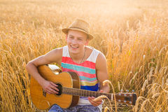 A man is playing guitar in the field at relax day with sun light. Stock Photography