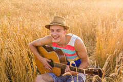 A man is playing guitar in the field at relax day with sun light. Royalty Free Stock Photography