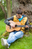 Man playing on guitar in forest Royalty Free Stock Photos