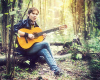 Man playing guitar in forest Stock Image