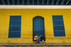 Man playing the guitar in front of one of the colonial buildings Royalty Free Stock Photos