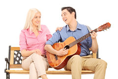 Man playing guitar for a girl seated on bench Stock Photography