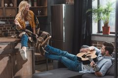 Beautiful young handsome man playing guitar for girlfriend. At kitchen royalty free stock photo