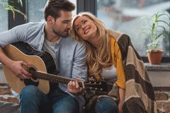 Handsome man playing guitar for girlfriend. At home stock photography
