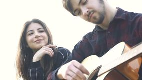 Man playing the guitar for girlfriend. Outdoor. Girl listening song. Romantic couple sitting and man playing the guitar and singing for girlfriend. Outdoor stock footage