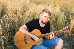 A man is playing guitar in grass field at relax day with sun light Stock Photo