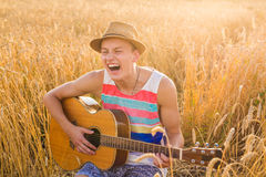 A man is playing guitar in grass field at relax day with sun light Stock Photography