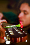 Man playing guitar, guitar with red flowers of carnations. Royalty Free Stock Photo
